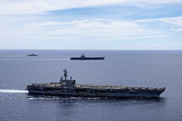 米軍は南シナ海での軍事演習や航行の自由作戦を活発化させている(写真は同海域を航行する空母ロナルド・レーガン(前)と同ニミッツ=AP)