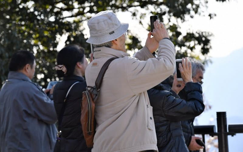高尾山頂で写真を撮る高齢者(東京都八王子市)