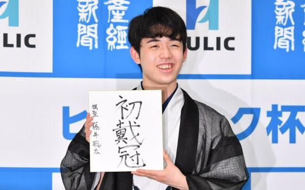 最年少でタイトルを獲得し、色紙を手に笑顔の藤井聡太新棋聖(7月16日、大阪市の関西将棋会館)