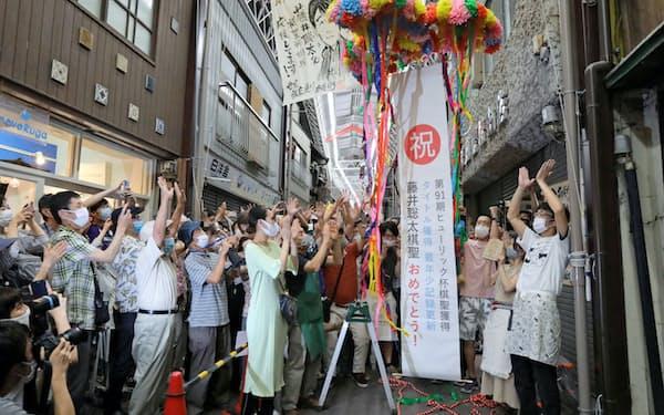 藤井聡太七段の地元・愛知県瀬戸市では、住民がくす玉を割ってタイトル獲得を祝った(16日夜)