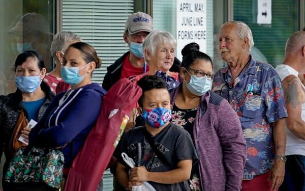 ケンタッキー州で行政の支援を求めて行列するマスク姿の失業者ら(6月)=ロイター