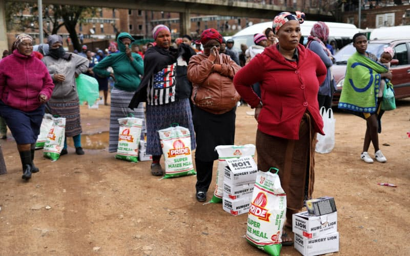 新型コロナウイルス対策として配られた支援物資を受け取るために列を作る南アフリカの人々=ロイター