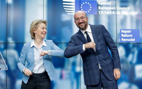 記者会見後、笑顔で撮影に応じたミシェルEU大統領(右)とフォンデアライエン欧州委員長(21日、ブリュッセル)=ロイター