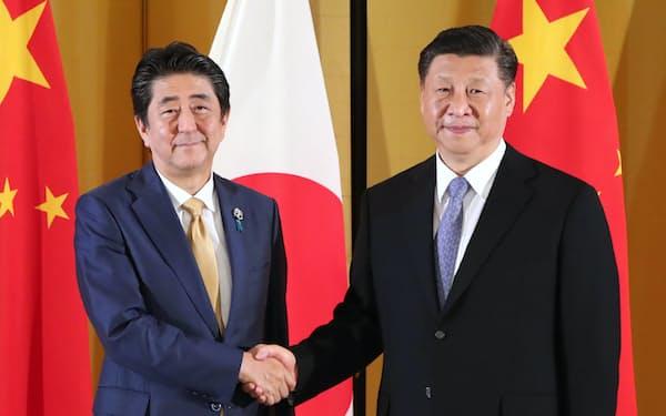 中国の習近平国家主席(右)と握手する安倍首相(2019年6月27日、大阪市)=代表撮影