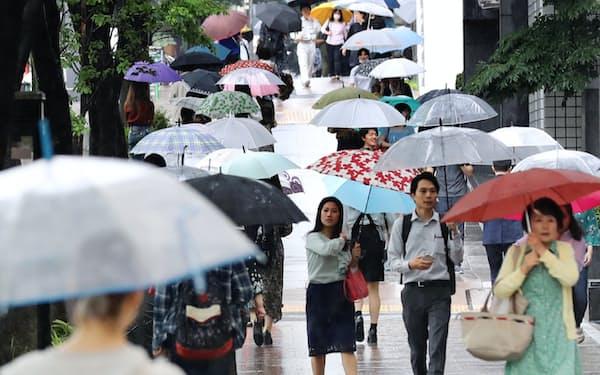 梅雨空の下、傘を差して歩く人たち(7日午後、名古屋市中区)