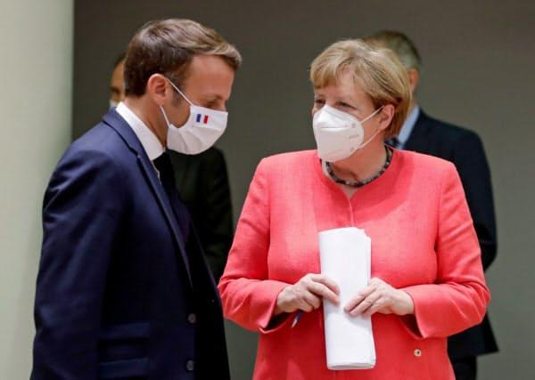 懇談するメルケル独首相とマクロン仏大統領(21日)=ロイター