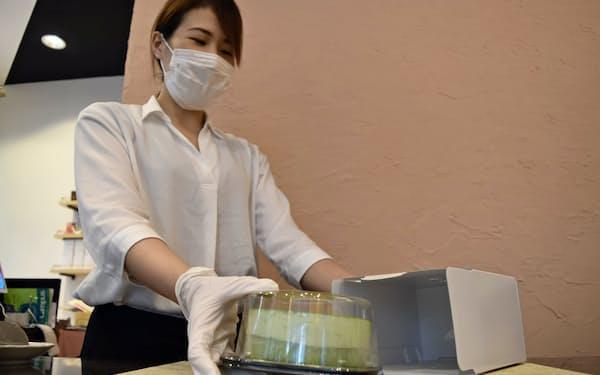 通信販売向けにケーキを梱包する「大三萬年堂 HANARE」のスタッフ(東京・千代田)