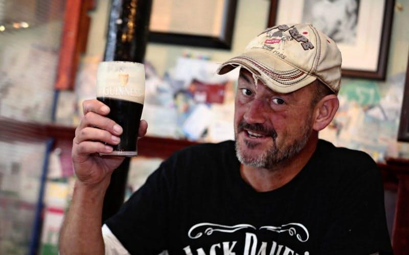 コロナウイルス対策の営業規制が緩和され、パブでギネスビールを楽しむアイルランドの男性(6月、ダブリン)=AP