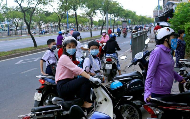 バイクで送迎するなど子供に世話を焼く親が多い(ホーチミン市)=ロイター