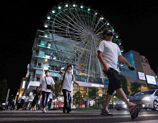 22日夜、名古屋市の繁華街をマスク姿で歩く人たち=共同
