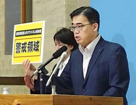 感染状況について記者会見する愛知県の大村秀章知事(23日午後、愛知県庁)=共同