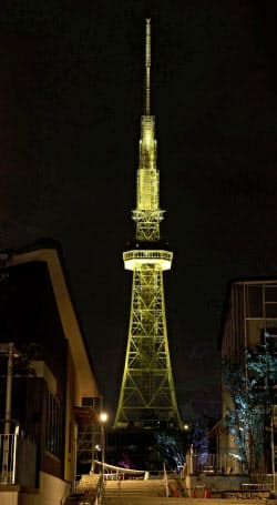 警戒を促すため、黄色にライトアップされた「名古屋テレビ塔」(23日夜、名古屋市)=共同