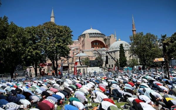 24日、アヤソフィアの外で祈りを捧げる人々(イスタンブール)=アナトリア通信