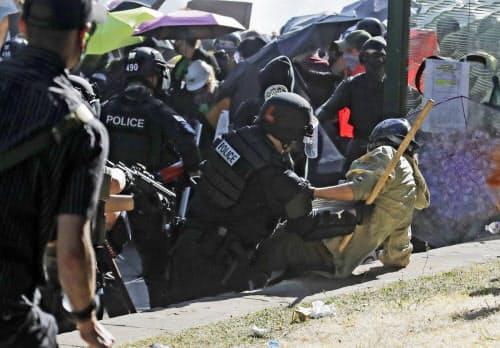 抗議デモ参加者を地面に押さえつけ鎮圧する警察(25日、米西部ワシントン州シアトル)=AP