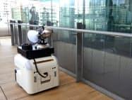 駅構内の手すりを自律走行で消毒するロボット(27日、東京都港区)