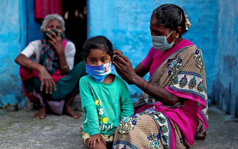 ニューデリーで子供に感染防止のためにマスクを付ける女性=ロイター