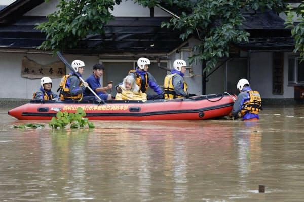 大雨で浸水した住宅地からゴムボートで救助される人たち(28日午後5時54分、山形県大江町)=共同
