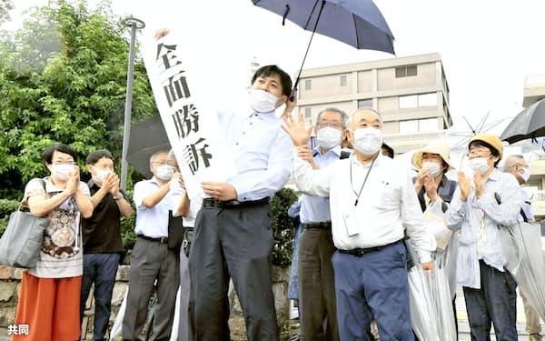 「黒い雨」訴訟で全面勝訴し、広島地裁前で喜ぶ原告団(29日、広島市)=共同