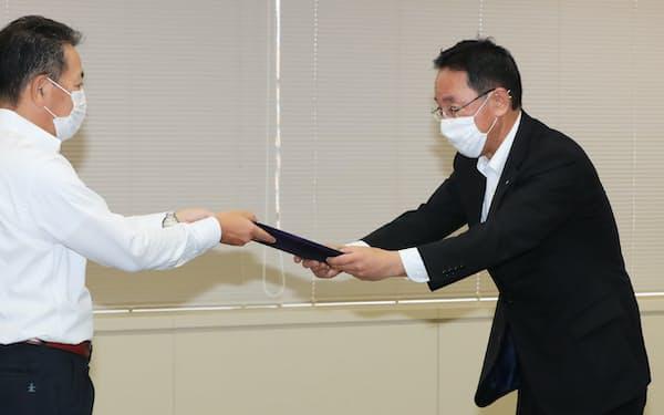 使用済み核燃料再処理工場の安全審査に合格し、許可書を受け取る日本原燃の増田尚宏社長(右)(29日、東京都港区)