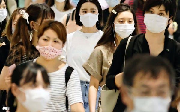 西鉄福岡駅でマスクを着けて歩く人たち(22日、福岡市)=共同