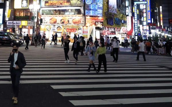 夜の繁華街を行き交う人たち(6月、東京都新宿区)