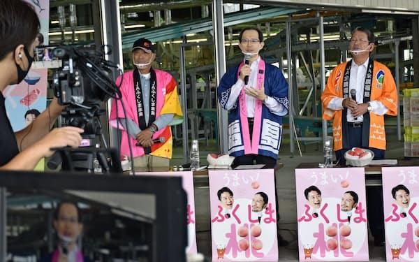 福島県産のモモをPRする内堀知事(中)ら(30日、福島市)