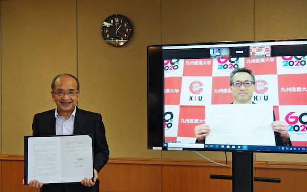 協定書を持つ大分県の広瀬勝貞知事(左)と九州産業大学の榊泰輔学長(30日、大分県庁)