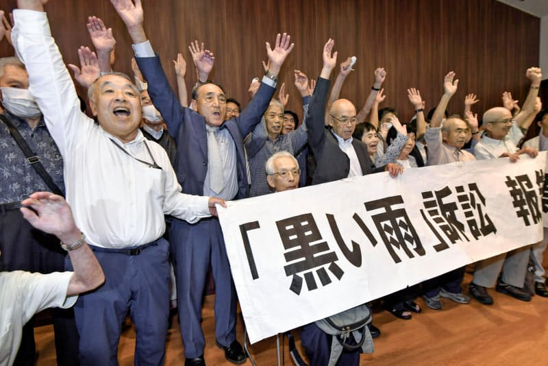 「黒い雨」訴訟で全面勝訴し、報告集会で万歳する(左から)訴訟を支援する会の高東征二事務局長、高野正明原告団長ら=29日午後、広島市