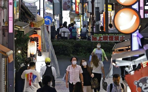 東京・新宿の繁華街をマスク姿で歩く人たち(30日夕)