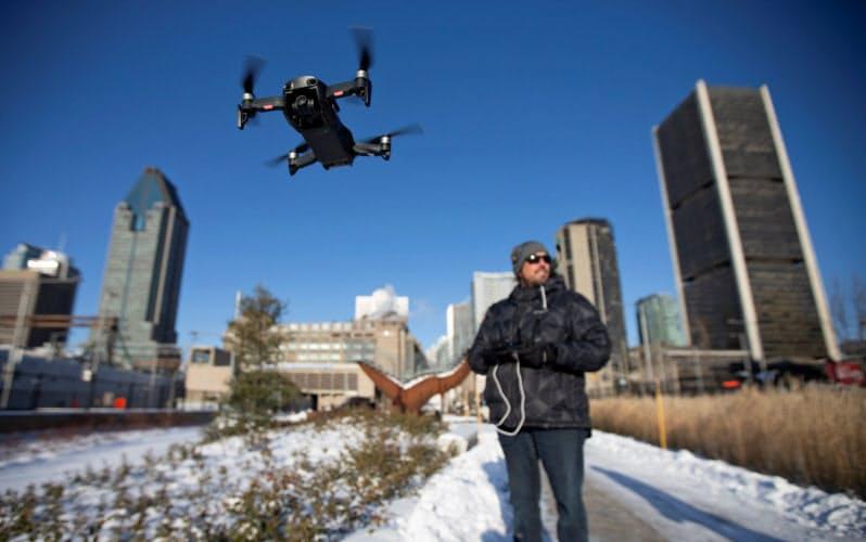 カナダ・モントリオールでDJI製のドローンをデモ飛行する男性。同社のドローンはノートルダム寺院の消防活動に活躍した=ロイター