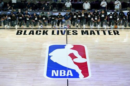 「ブラック・ライブズ・マター(BLM=黒人の命も大事だ)」と記されたコートに並び、片膝をつくペリカンズ、ジャズの選手ら(30日、フロリダ州オーランド近郊)=AP