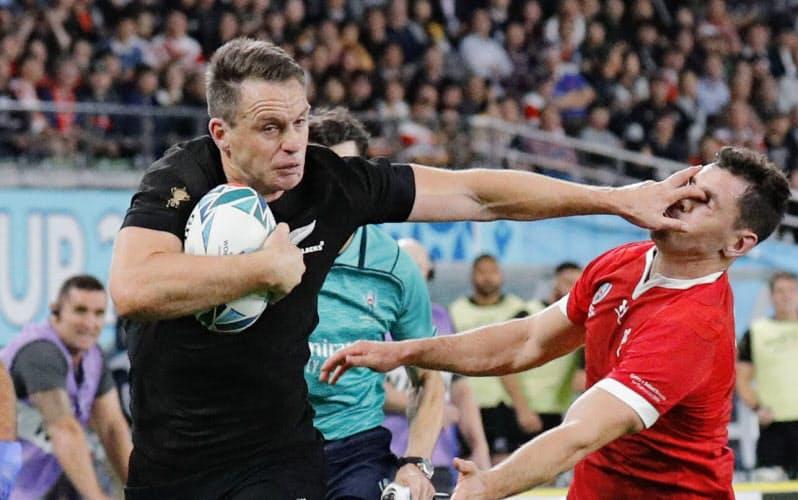 ラグビーW杯日本大会のウェールズ戦で、ハンドオフで振り切りトライを決めるニュージーランドのベン・スミス(2019年11月1日、味の素スタジアム)=共同