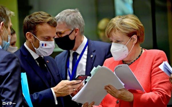 EU首脳会談で懇談するメルケル独首相(右)とマクロン仏大統領=ロイター