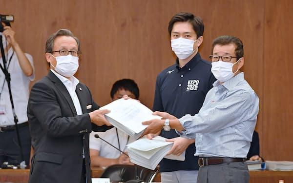 今井会長(左)から協定書を受け取った松井大阪市長(右端)と吉村大阪府知事(31日、大阪市役所)