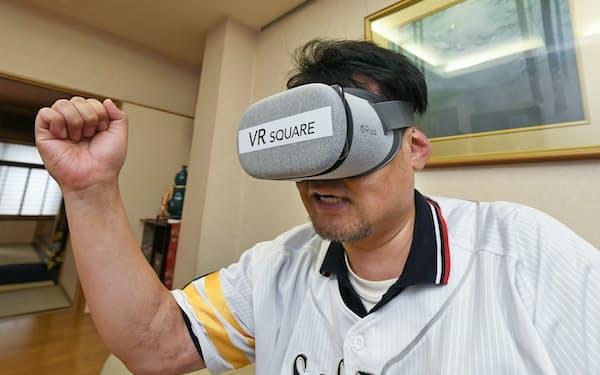 VRゴーグルを使い、自宅リビングで野球観戦を楽しむ近藤誠さん(東京都台東区)