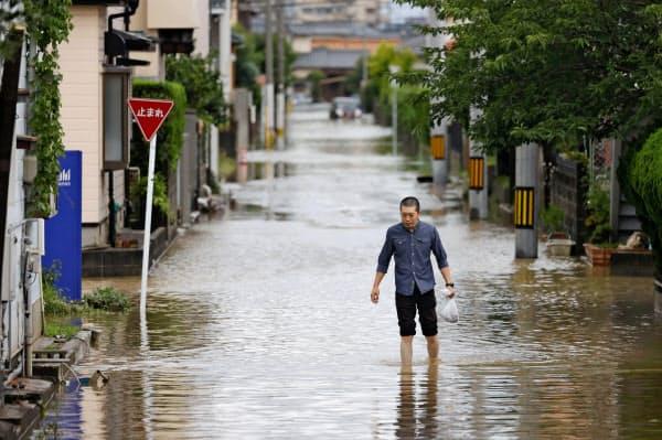 福岡県大牟田市で、冠水した住宅街を歩く男性(7月7日午後)=共同