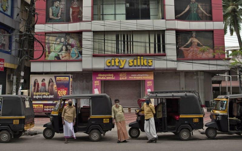 新型コロナの感染拡大で閉鎖された店舗の前で客を待つ三輪タクシーの運転手ら(ケララ州コチで)=AP