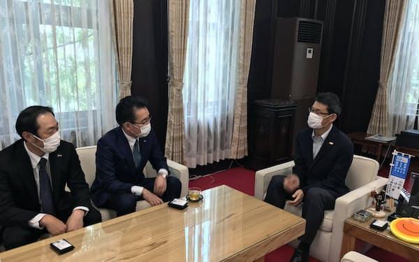 新規上場した日本情報クリエイトの米津健一社長(中)は、宮崎県の河野俊嗣知事(右)を表敬訪問した(3日、宮崎県庁知事室)