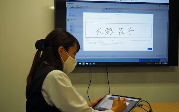 顧客がタブレット上で電子サインをするなどで業務を大幅にデジタル・ペーパーレス化(行員によるデモ)