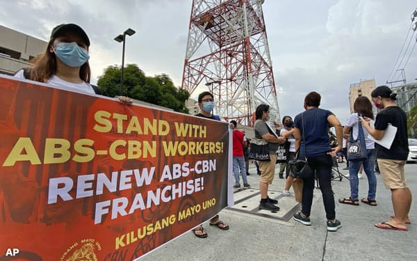 ABS-CBNの本社前で免許更新否決に抗議する支持者ら(7月10日、マニラ)=AP