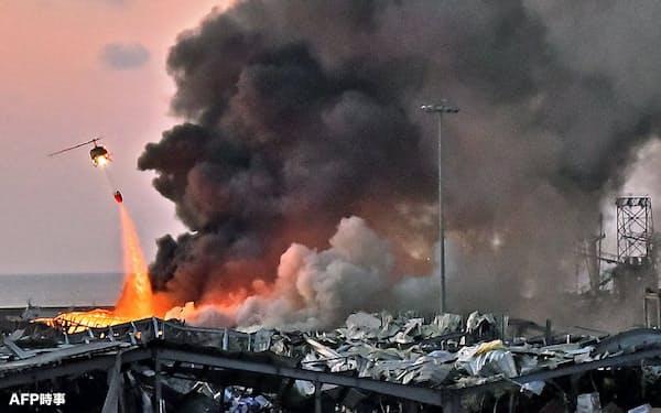 4日、レバノンの首都ベイルートの爆発現場で、消火活動に当たるヘリコプター=AFP時事