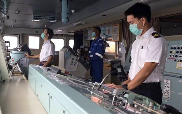 ソーシャルディスタンスを空けて操船する日本郵船のフィリピン人船員(右)