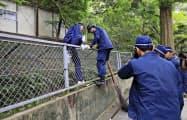 イノシシを捜す福岡県警の警察官(5日午前、福岡市)=共同