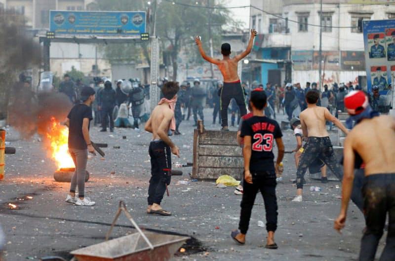 イラク治安部隊と衝突するデモ参加者(7月27日、バグダッド)=ロイター
