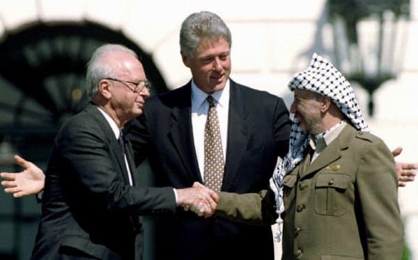 暫定自治宣言の調印式に臨むクリントン大統領(中)。敵対するパレスチナ解放機構(PLO)のアラファト議長(右)とイスラエルのラビン首相が握手を交わした(1993年、ワシントン)=ロイター