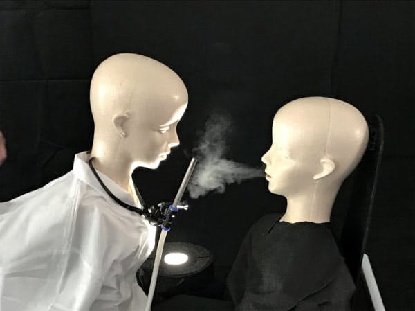 ノズルからの気流で医師らの口元に空気の壁をつくり、患者の吐く息を遮断する
