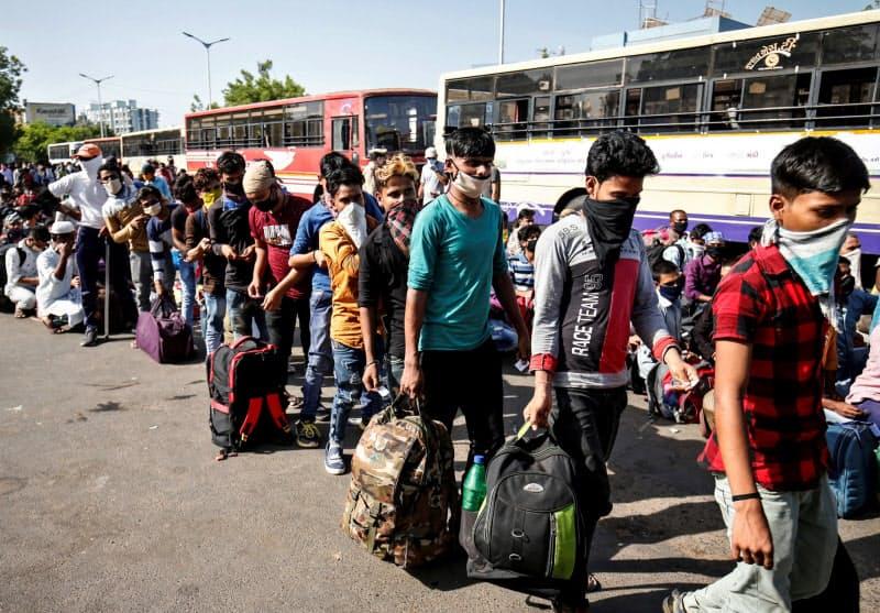 ロックダウンで出稼ぎ労働者の多くが都市部を離れた(5月、インド西部のアーメダバードでバスに乗り込む労働者ら)=ロイター