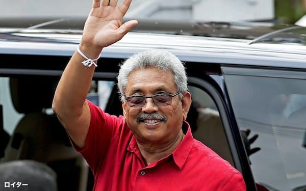 スリランカ議会選で投票後、支持者に手を振るラジャパクサ大統領(5日、コロンボ)=ロイター