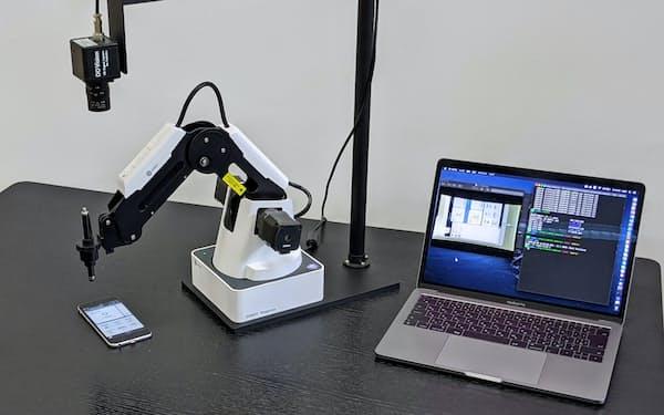 ロボットアーム(左)でスマートフォンを操作し、アプリの不具合を監視する