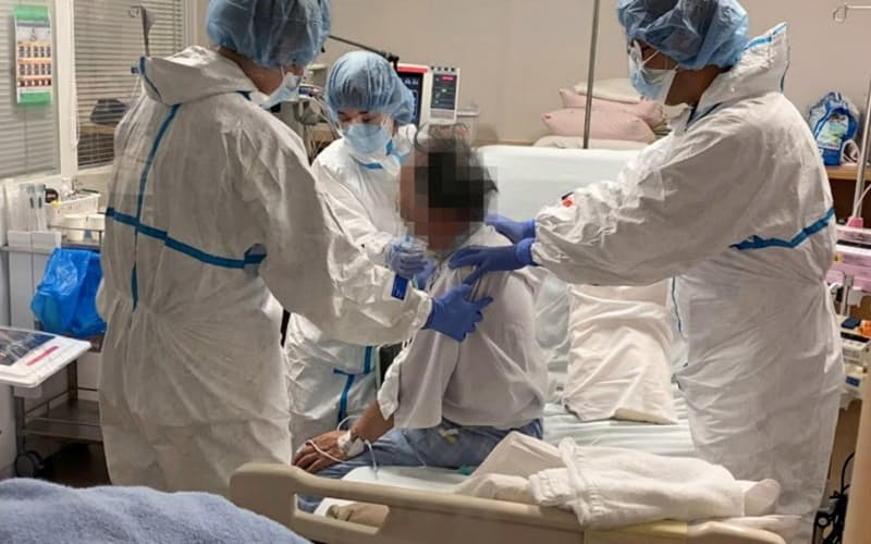 新型コロナの重症患者がICUの中でリハビリに取り組む。2人の理学療法士が体やチューブを支えている。(神戸市立医療センター中央市民病院提供)